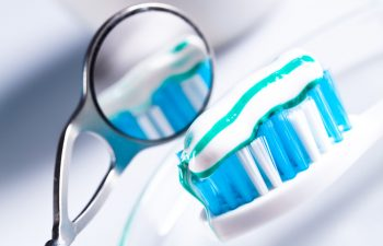 A dental mirror next to a toothbrush with toothpaste